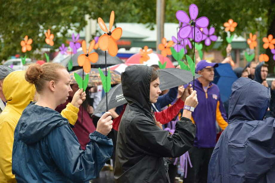 Despite cold temperatures and a steady rain, around 300 individuals turned up for the Alzheimer's Walk for a Cure Saturday at Community Park. Holding flowers, each color signifying the way that individual has been affected by the disease, the group walked the park and raised $23,000 toward a cure. Though short of their $36,000 goal, the group will continue raising funds through December. Photo: Nick Draper | Journal-Courier