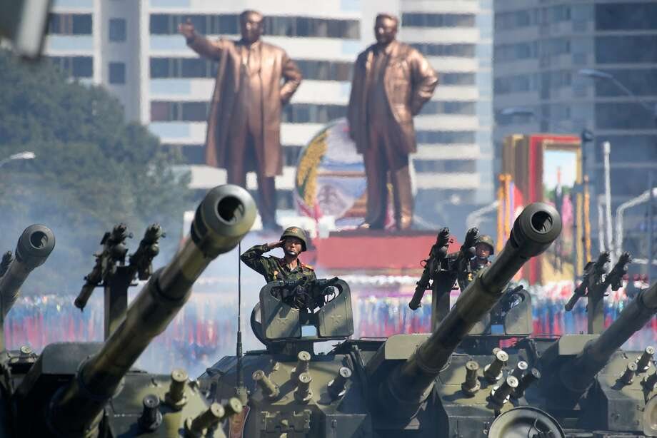 North Korean soldiers salute as they ride tanks during a military parade and mass rally in Pyongyang. Photo: Ed Jones / AFP / Getty Images
