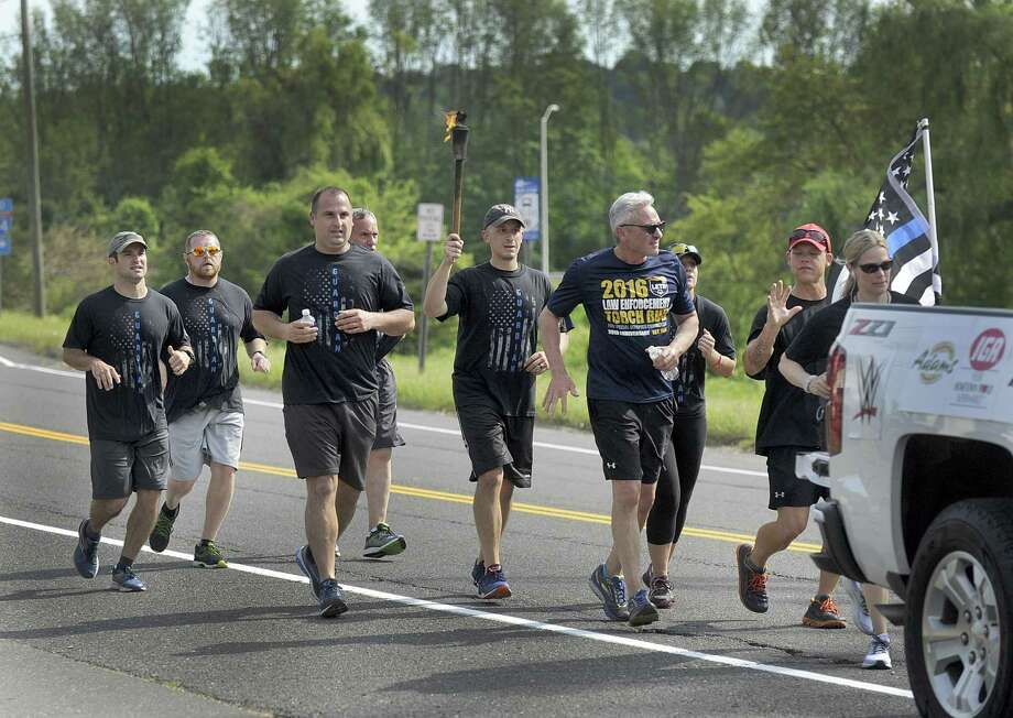 """The Law Enforcement Torch Run for Special Olympics Connecticut, which is celebrating its 50th anniversary, passes through Brookfield Friday morning, June 8, 2018. Police officers will cumulatively run more than 530 miles through over100 towns for Special Olympics during June 6-8. It's stated mission is a serious commitment by the law enforcement community to pay homage to """"our heroes"""" - Special Olympics Connecticut athletes and their families. Photo: Carol Kaliff / Hearst Connecticut Media / The News-Times"""