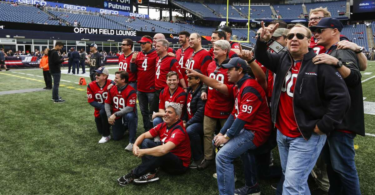 A group of Houston Texans fans line up to take a group picture on the sidelines before an NFL football game against the New England Patriots at Gillette Stadium on Sunday, Sept. 9, 2018, in Foxborough, Mass.