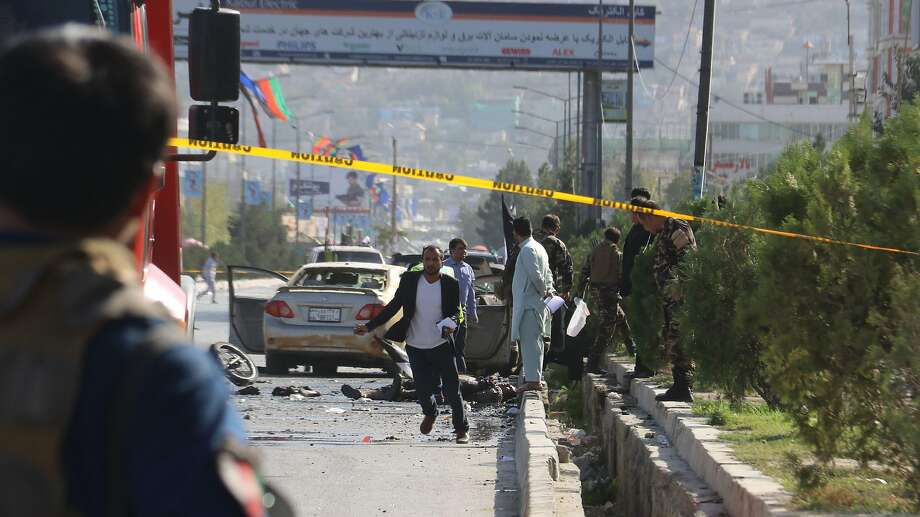 Security personnel examine the scene of a suicide attack in Kabul. The bomber blew himself up near a convoy of gunmen commemorating the anniversary of a famed resistance leader's death. Photo: AFP / Getty Images
