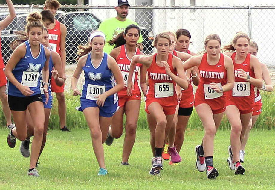 Staunton girls run with Marquette Catholic at the start of the Carlinville Early Meet on Aug. 29 in Carlinville. Staunton's No. 1 runner Lydia Roller sat out the early meet, but rejoined her teammates Saturday in Peoria where more than 2,000 boys and girls competed in the First to the Finish Invitational at Detweiller Park. Photo: Greg Shashack / The Telegraph