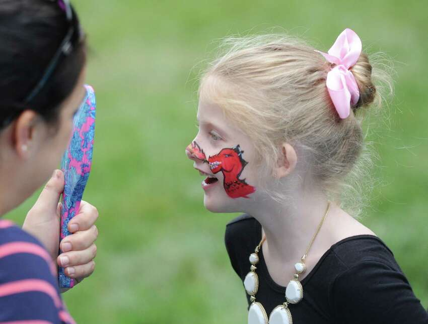 Greenwich's Molly Garan, 7, takes a look at her new face paint at the annual homecoming weekend at Second Congregational Church in Greenwich, Conn. Sunday, Sept. 9, 2018. The church held a special outdoor service featuring music from the Astrograss bluegrass band, a buffet-style feast and games and activities for kids.