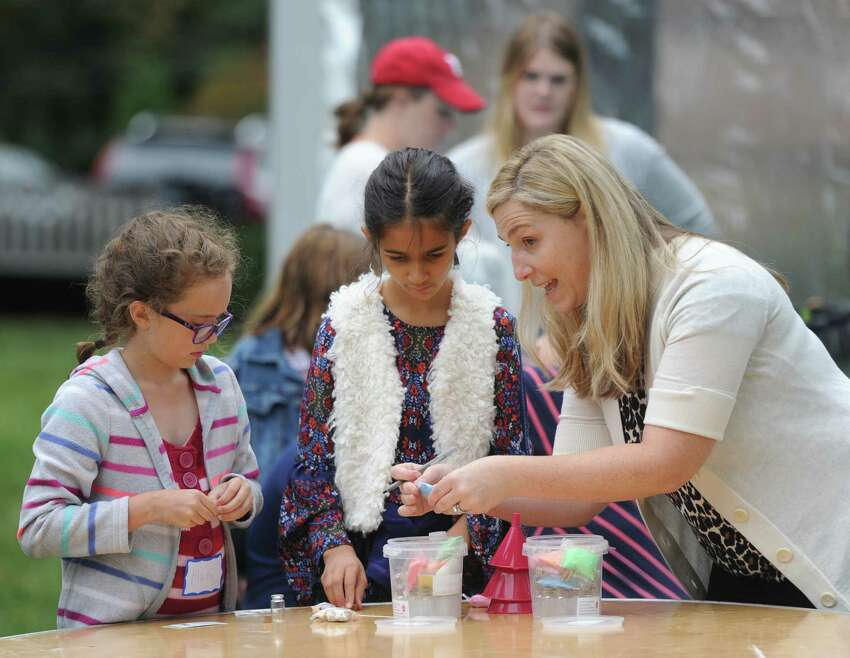 Jessica Stanciu helps Maren Huppunen, left, 10, of Stamford, and Arya Pelletier, 9, of Greenwich, with a project at the annual homecoming weekend at Second Congregational Church in Greenwich, Conn. Sunday, Sept. 9, 2018. The church held a special outdoor service featuring music from the Astrograss bluegrass band, a buffet-style feast and games and activities for kids.