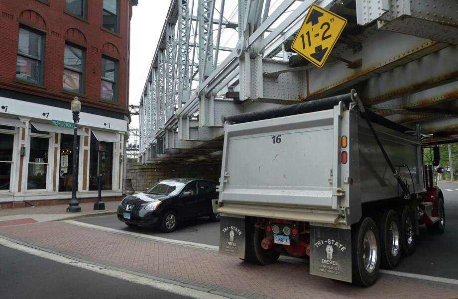 Trucks drive under the Metro-North Railroad Bridge at the intersection of Washington and North and South Main Streets Friday, August 17, 2018, in Norwalk, Conn. Trucks that exceed the clearance strike the bridge at least once a month. Now, the Norwalk Department of Public Works is planning to partner with the state to install a laser-warning system. Photo: Erik Trautmann / Hearst Connecticut Media / Norwalk Hour