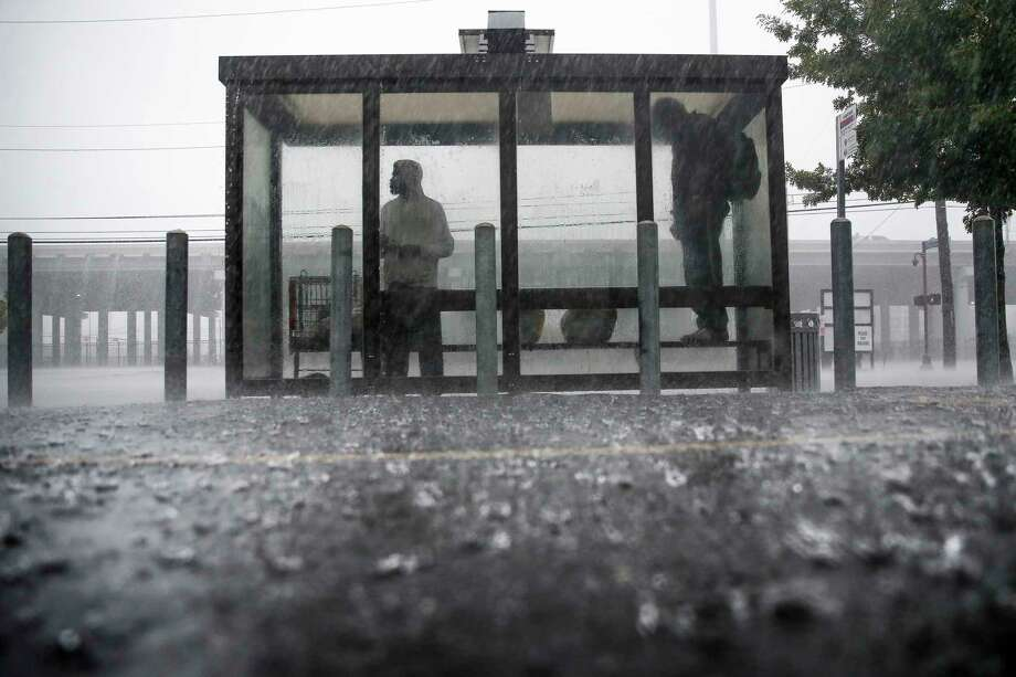 People take cover under a bus stop on Hamilton Street as heavy rain falls over the downtown area Sunday Sept. 9, 2018 in Houston. Photo: Michael Ciaglo, Staff Photographer / Michael Ciaglo