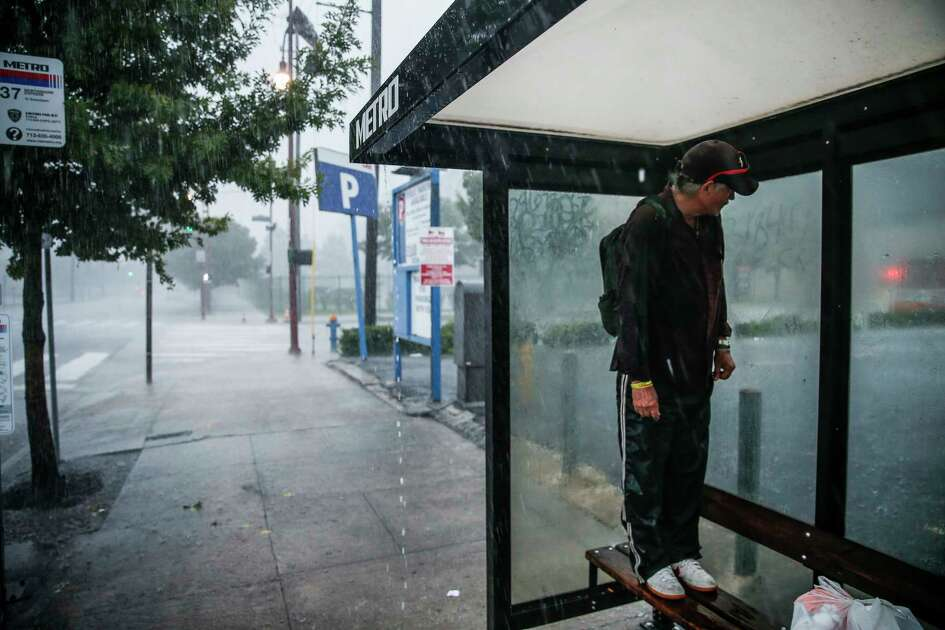 A man stands on a bus stop bench on Hamilton Street as he avoids the heavy rain falling over the downtown area Sunday Sept. 9, 2018 in Houston.