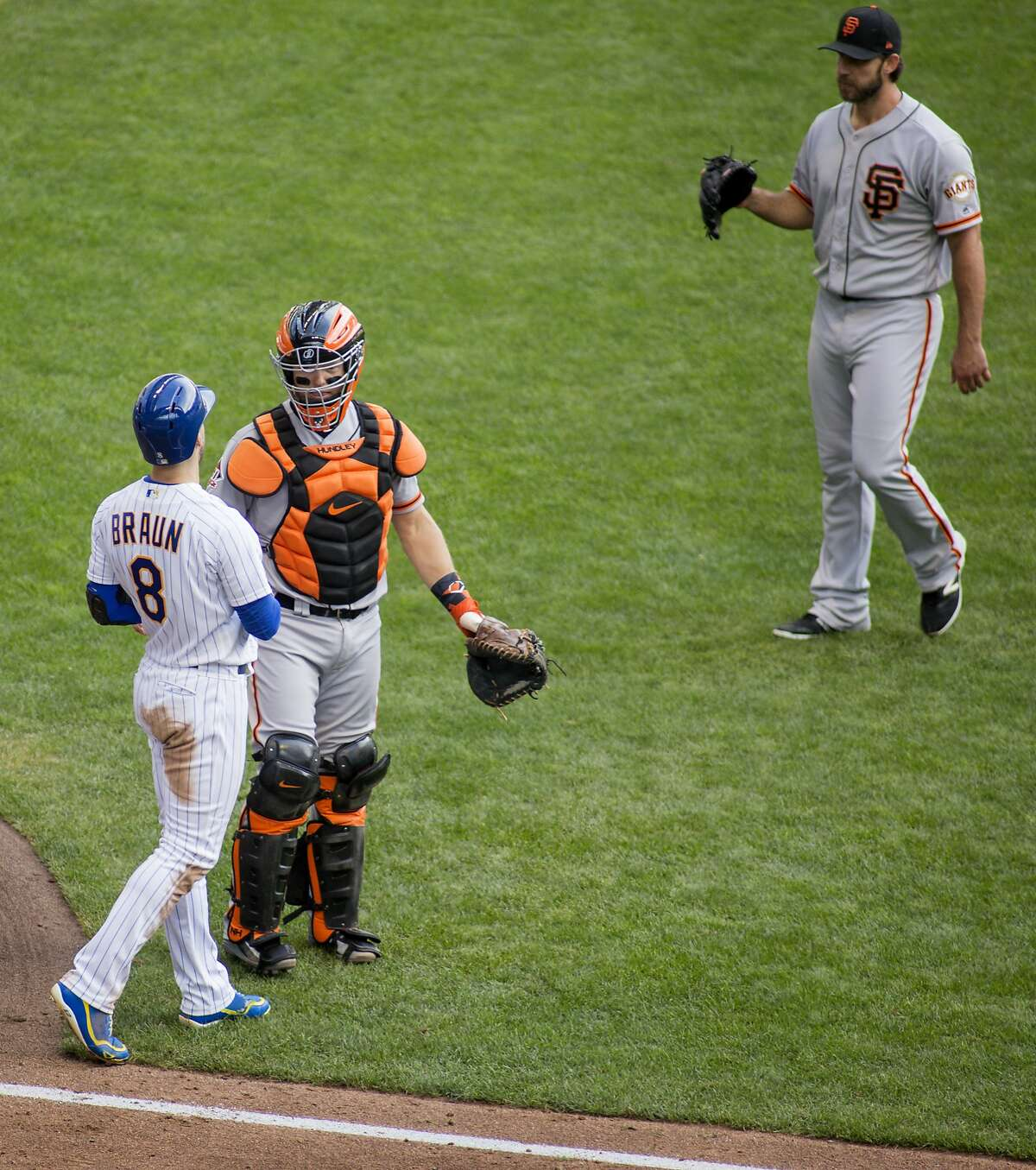 Milwaukee Brewers' Ryan Braun, left, reacts to San Francisco Giants' Madison Bumgarner, right, after being hit by a pitch during the sixth inning of an baseball game Sunday, Sept. 9, 2018, in Milwaukee. (AP Photo/Darren Hauck)