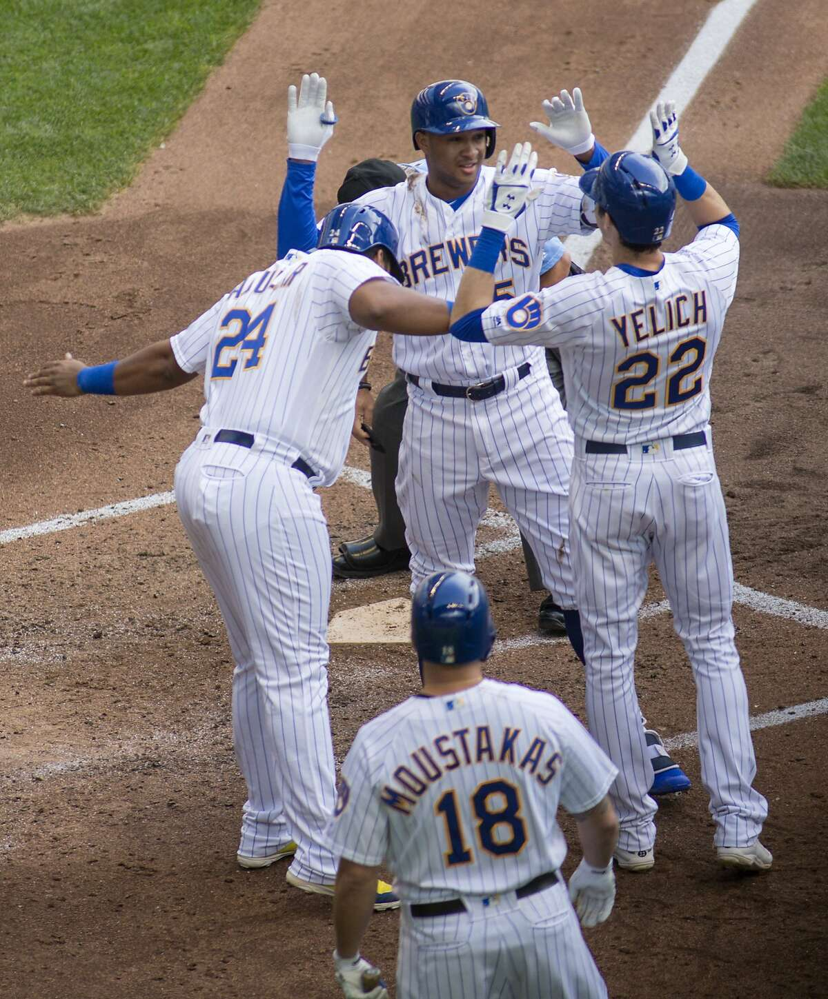 Milwaukee Brewers' Jonathan Schoop, top center, is congratulated by teammates after hitting a grand slam against the San Francisco Giants during the sixth inning of an baseball game Sunday, Sept. 9, 2018, in Milwaukee. (AP Photo/Darren Hauck)