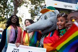 "Oakland A's ""Stomper"" and Oakland Mayor Libby Schaaf pose with Oakland Pride parade participants in Oakland, Calif. on Sunday, September 9, 2018."