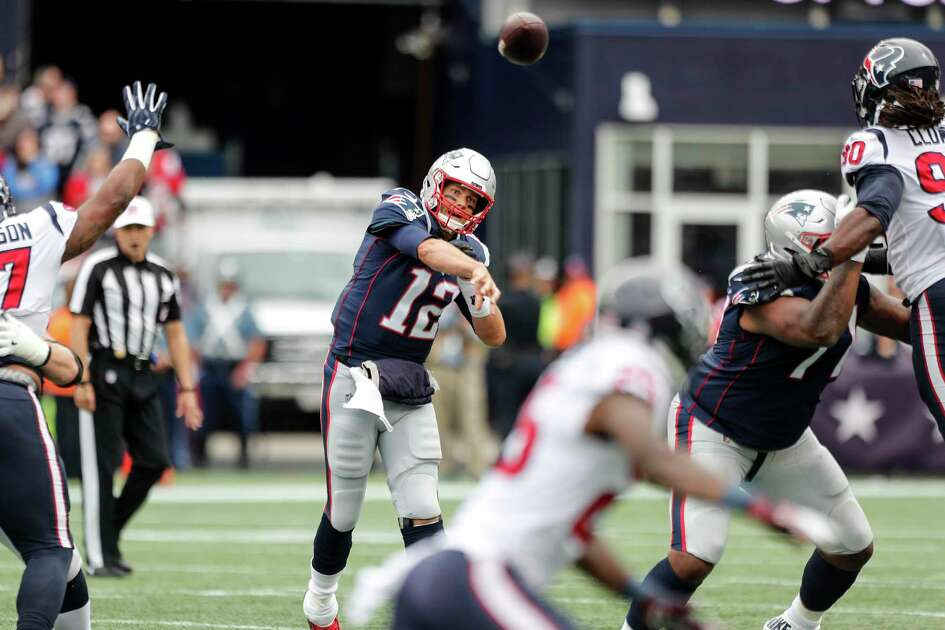 New England Patriots quarterback Tom Brady (12) throws a pass as he is rushed by Houston Texans defensive end Jadeveon Clowney (90) during the first quarter of an NFL football game at Gillette Stadium on Sunday, Sept. 9, 2018, in Foxborough, Mass.