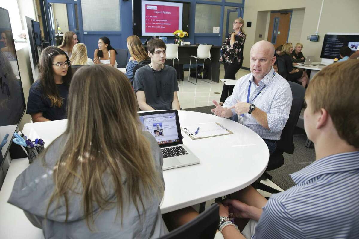 Business Incubator Team Inflection Point representative Henry Sauer talks with a group as Alamo Heights students participate in a class called Business Incubator wherein groups work on a business presentation and present it to real business people visiting the school on September 5, 2018.