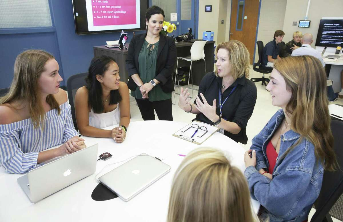 Hemisfair Conservancy Executive Director Anne Krause offers her observations as Alamo Heights students participate in a class called Business Incubator wherein groups work on a business presentation and present it to real business people visiting the school on September 5, 2018. Students from left are Helen Hunter, Mia McEwen, Katy McKenna (foreground) and Sember Lucas (right). Business Incubator lead teacher Patrice Bartlett stands and listens to the group's topic which involves ideas about cooling automobile interiors while they are parked.