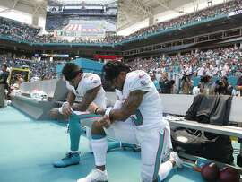 Miami Dolphins wide receiver Kenny Stills (10) and Miami Dolphins wide receiver Albert Wilson (15) kneel during the national anthem before an NFL football game against the Tennessee Titans, Sunday, Sept. 9, 2018, in Miami Gardens, Fla. (AP Photo/Wilfredo Lee)