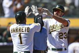 Oakland Athletics' Franklin Barreto, left, and Matt Joyce (23) celebrate after scoring against the Texas Rangers in the fourth inning of a baseball game Sunday, Sept. 9, 2018, in Oakland, Calif. Both scored on a single by A's Nick Martini. (AP Photo/Ben Margot)