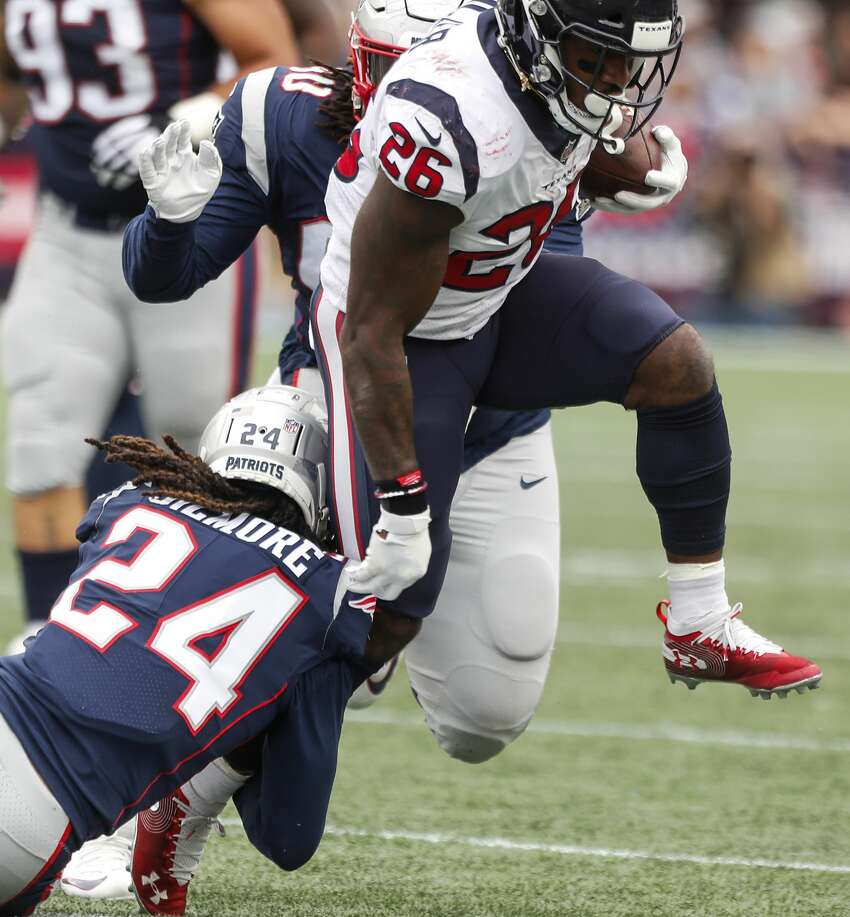 Houston Texans running back Lamar Miller (26) is hit by New England Patriots cornerback Stephon Gilmore (24) during the fourth quarter of an NFL football game at Gillette Stadium on Sunday, Sept. 9, 2018, in Foxborough, Mass.