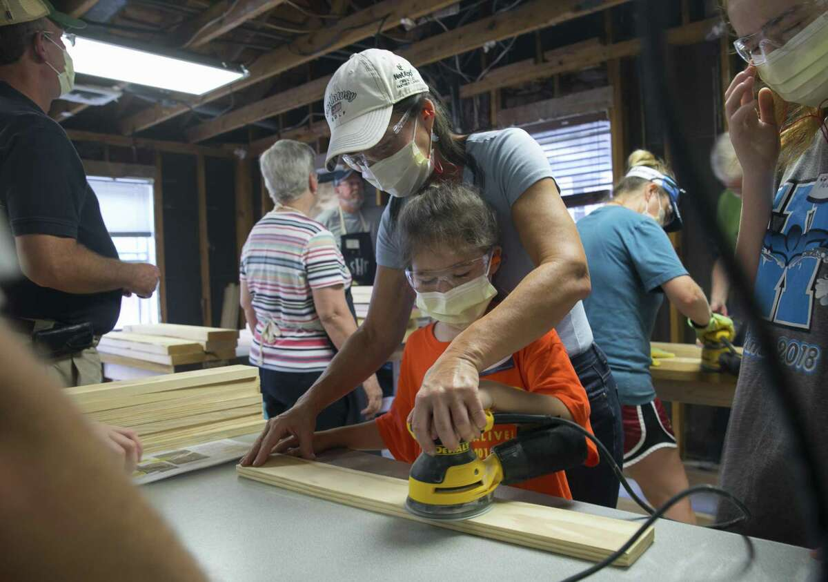 Lori McCray assists her 8-year-old daughter Sloane sand wooden slats during the second bunk bed build of the Northwest Houston Chapter of the Sleep in Heavenly Peace organization on Saturday, Sept. 8, 2018, in Cypress.