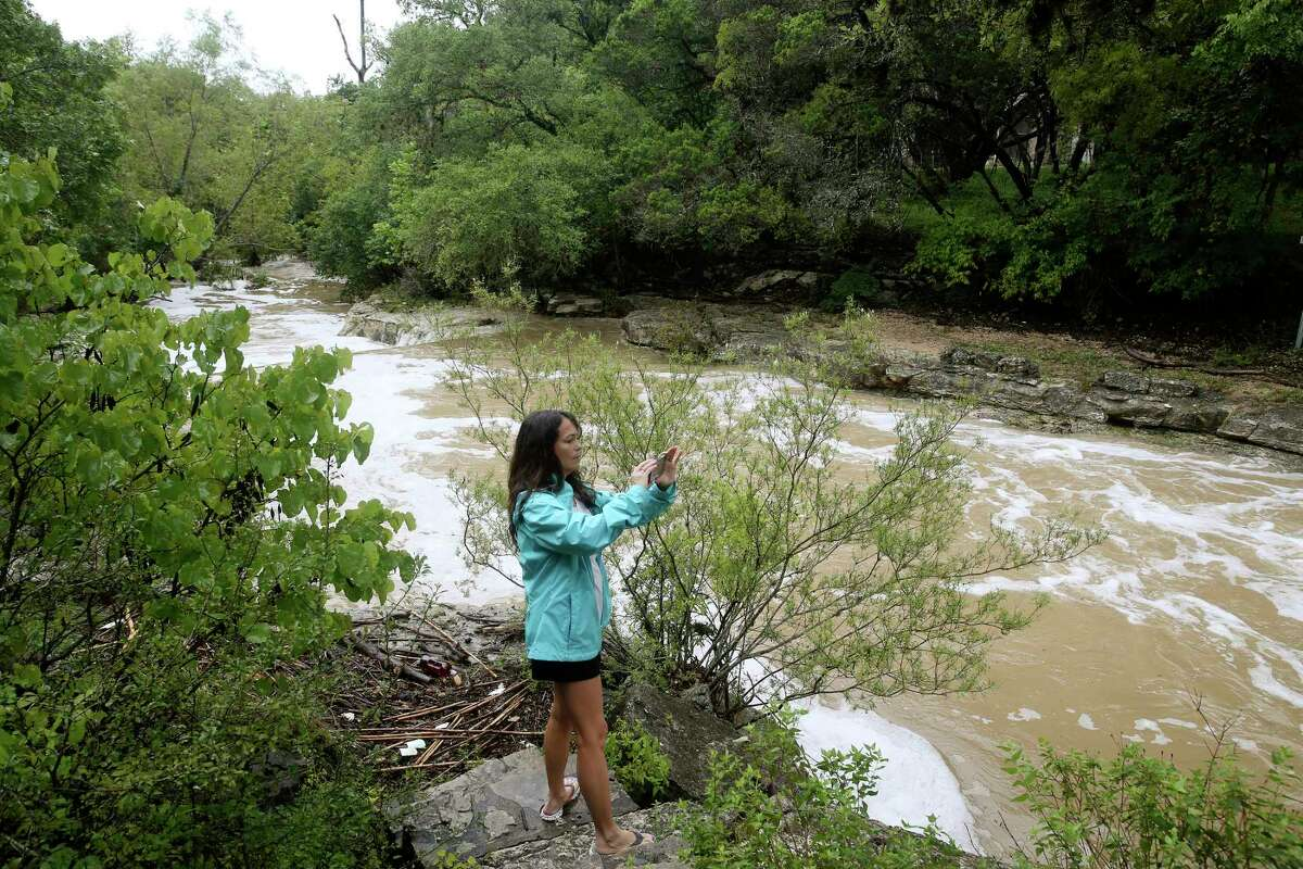 Kat Gehrke watches a flooded Helotes Creek in Grey Forest after rains causes flooding at low water crossings throughout the town, Sunday, Sept. 9, 2018. At the height of the rain storm, all low water crossings, including the main road leading into Grey Forest, Scenic Loop Road, were closed for several hours.