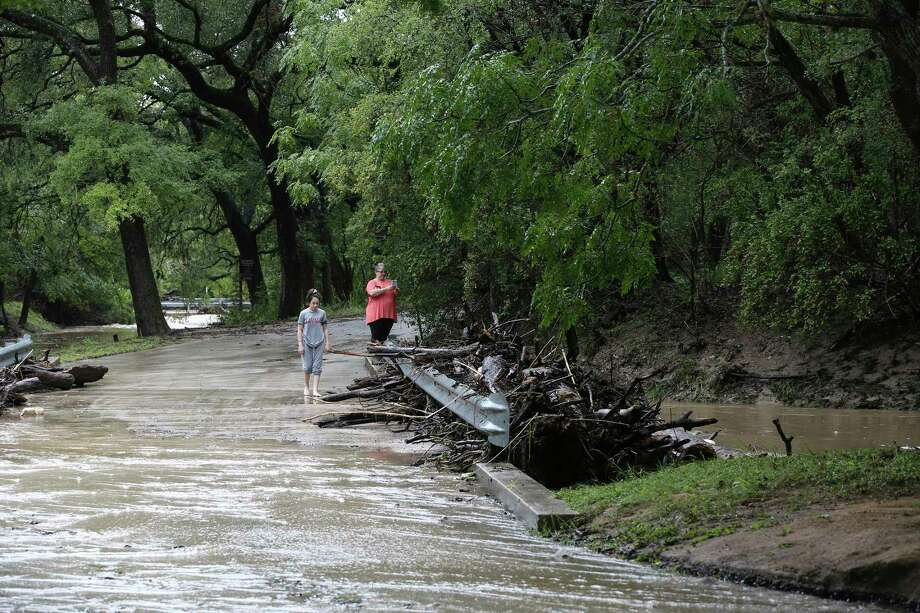Grey Forest residents photograph debris at low water crossing, Sunday, Sept. 9, 2018. All low water crossings in Grey Forest were closed due to flooding Sunday morning. At the height of the storm, the main road leading into town, Scenic Loop Road, was closed for several hours. Photo: JERRY LARA, San Antonio Express-News / © 2018 San Antonio Express-News