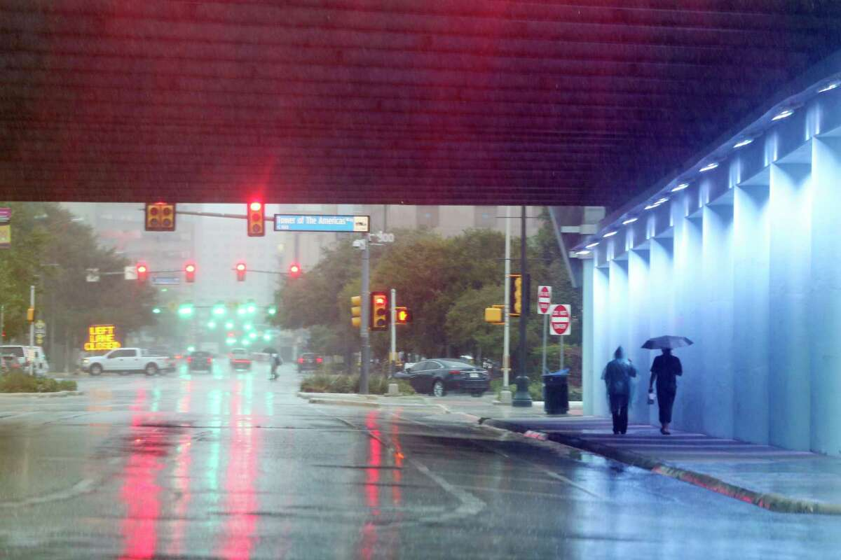As rains falls, pedestrians walk under the East Commerce Street/IH-37 overpass, Sunday, Sept. 9, 2018. Heavy rainfall caused over 70 road closures in the area.