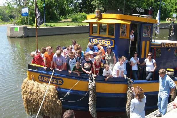 The historic tug Urger, built in 1901 and one of the oldest working tugs in the country and a floating classroom for school kids, is slated to be pulled from the water at Waterford and put on land at a new Thruway rest area at Exit 13, near Canajoharie, angering maritime historians.