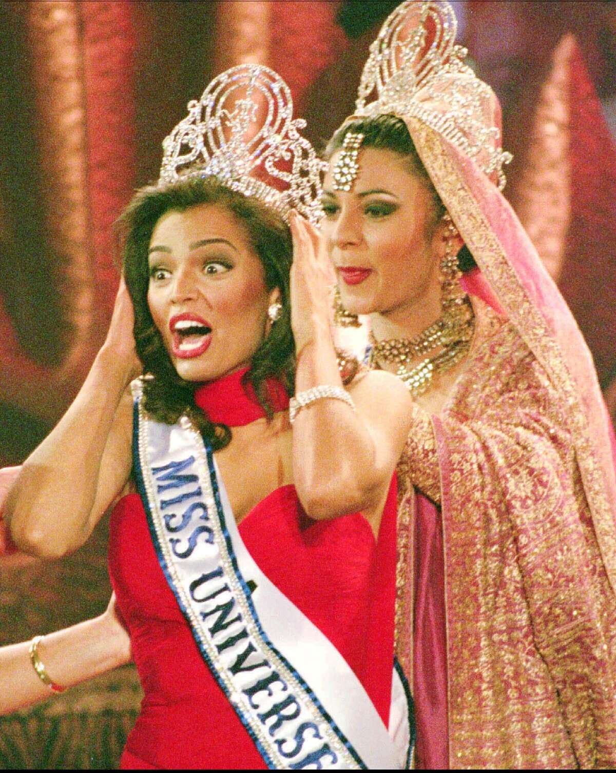 Miss USA Chelsi Smith, front, cries out for joy as she is crowned Miss Universe by the outgoing Miss Universe from India Sushmita Sen, at the conclusion of the Miss Universe pageant in Windhoek, Saturday May 13, 1995. (AP Photo/Adil Bradlow)