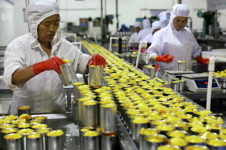 In this Aug. 31, 2018, photo, workers pack tinned peaches for export at a fruits processor in Huaibei city in central China's Anhui province. China's trade surplus with the United States widened to a record $31 billion in August as exports surged despite U.S. tariff hikes, potentially adding fuel to President Donald Trump's battle with Beijing over industrial policy. (AP Photo/Andy Wong) Photo: Andy Wong / Copyright 2018 The Associated Press. All rights reserved.