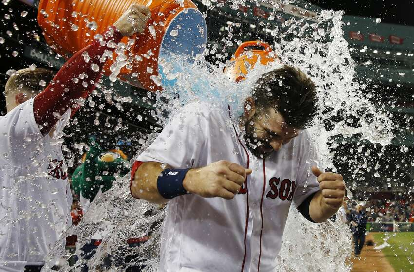 Boston Red Sox's Brock Holt, left, douses Mitch Moreland after Moreland's game-winning RBI single during the ninth inning of a baseball game against the Houston Astros in Boston, Sunday, Sept. 9, 2018. (AP Photo/Michael Dwyer)