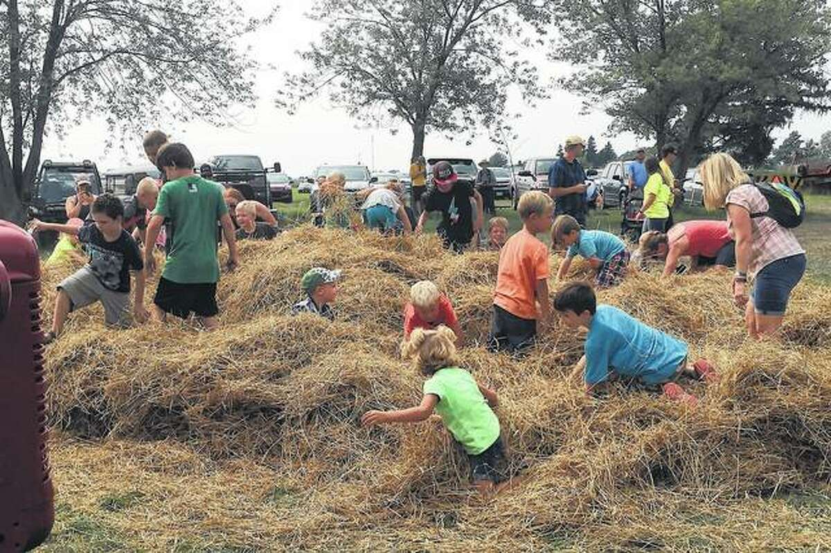 Children search for candy bags in the straw.