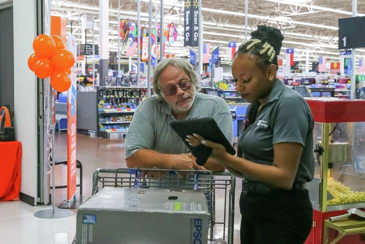 August 16, 2018: Shopper and Santa Fe resident Scott Mahon studies a comparison chart on a digital tablet while Directly Energy Team Leader Laporsha Woody explains cost usage breakdowns at the Walmart Supercenter in League City, Texas. (Leslie Plaza Johnson/For the Chronicle)