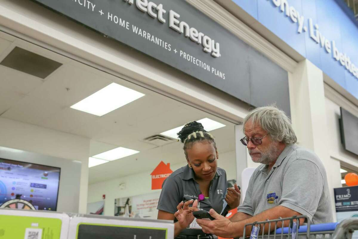 A Santa Fe resident shows a Direct Energy employee his energy bill at the Walmart Supercenter in League City, Texas. Direct Energy will layoff 54 workers this fall, the company said.