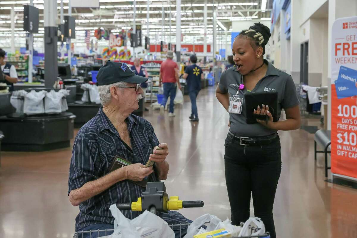 Direct Energy team leader Laporsha Woody speaks to a shopper about electricity at the Walmart Supercenter in League City in 2018. Such sales methods are being forced to shut down as the coronavirus pandemic grows.