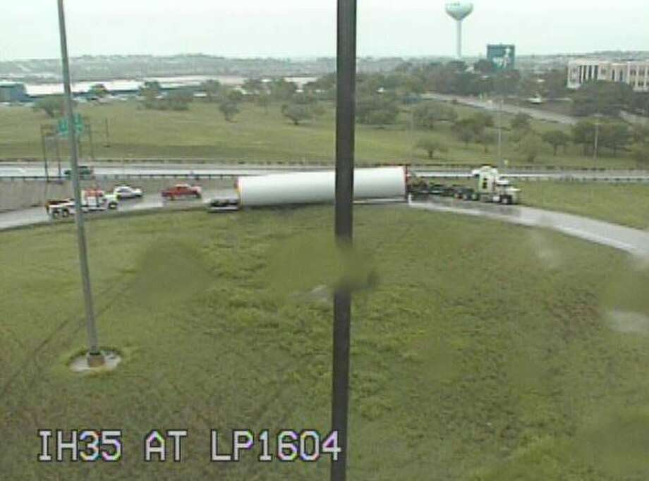 The truck flipped over around 10:45 a.m., prompting first responders to block the exit ramp as they try to remove it from the roadway. Photo: TxDOT
