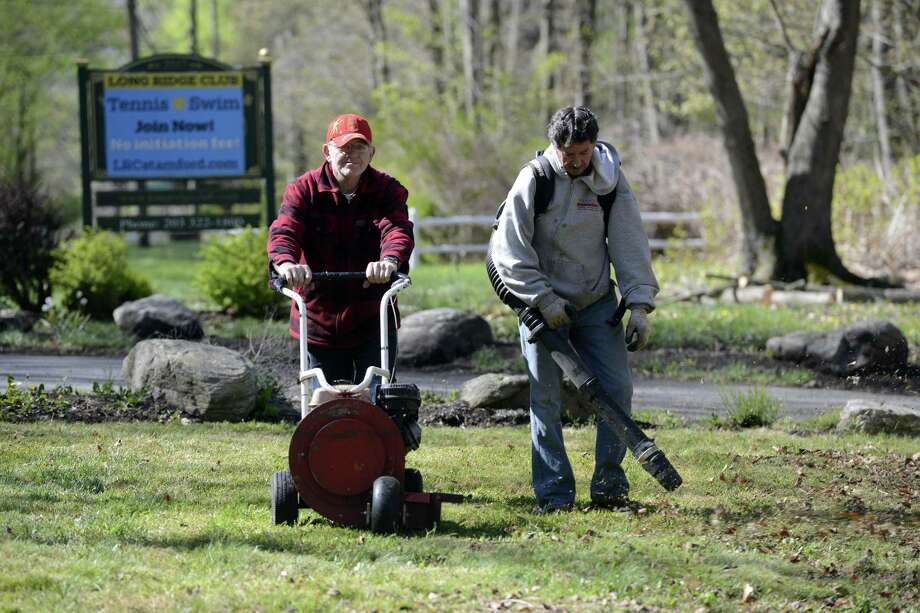 Camilo Eiomez and Fabio Velosquez help with the clean up efforts on April 30, 2016 at the Long Ridge Club in Stamford. The private swim and tennis clubwas preparing for its season opening on Sunday. Photo: Matthew Brown / Hearst Connecticut Media / Stamford Advocate