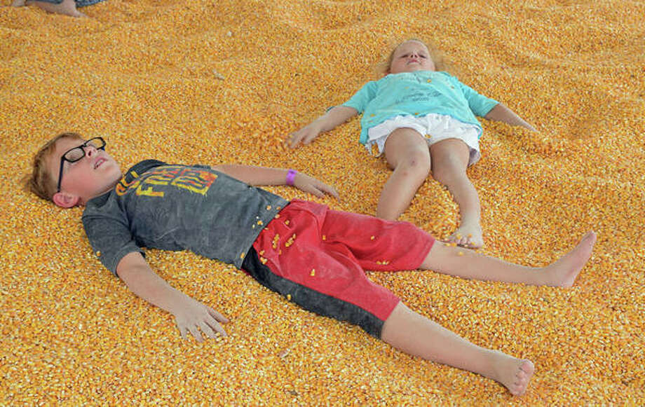 "Seven-year-old Tanner Mills and his four-year-old sister Natalie, both of Godfrey, play in the corn crib at Glazebrook Park for the Great Godfrey Maze during opening weekend. Though the recent holiday and inclement weather resulted in a bit of a revenue hardship — based on attendance — for the village's parks and recreation department, officials are ""optimistic"" about the reopening of the maze Friday, and the additional activities available to the public through Oct. 28. Photo: David Blanchette 