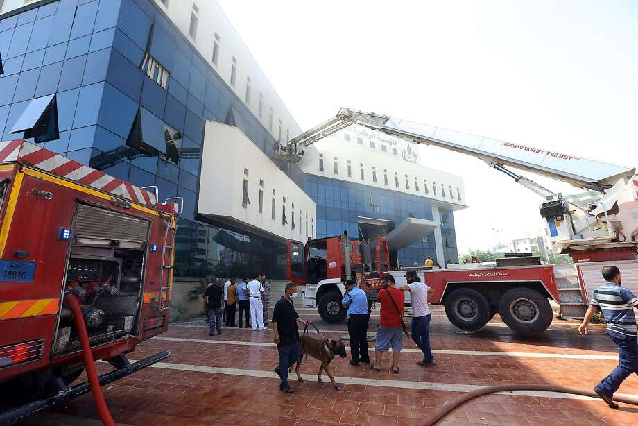 Firefighters and emergency responders gather at the scene of the attack on the Libyan National Oil Company in Tripoli. Local militia responded to the attack by besieging the building. Photo: Mahmud Turkia / AFP / Getty Images