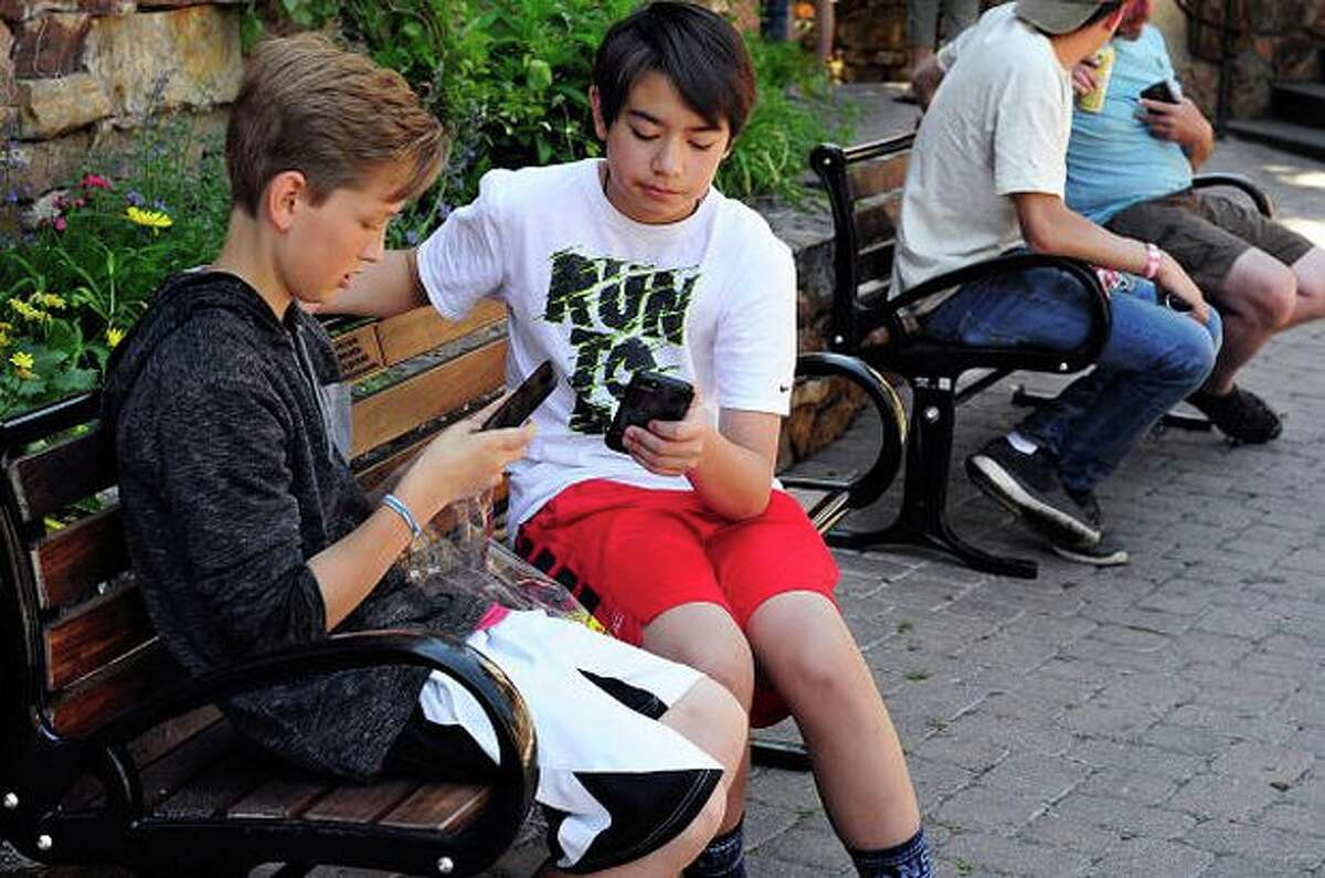 Two teenage boys use their smartphones as they sit on a bench.