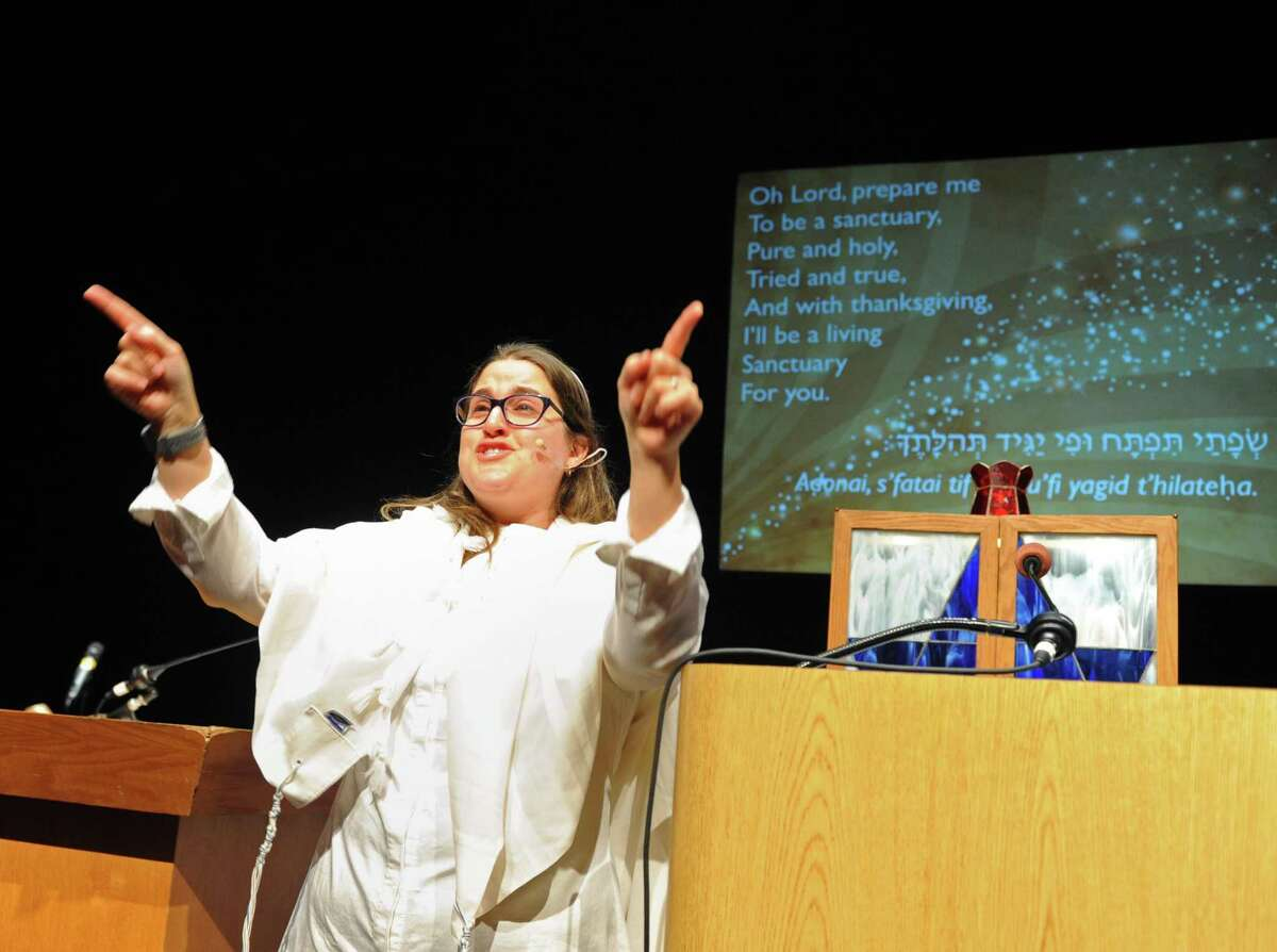 Rabbi Chaya Bender sings along to a song during Temple Sholom's Rosh Hashanah Family Service at Greenwich High School's Performing Arts Center in Greenwich, Conn. Monday, Sept. 10, 2018. The celebration of the Jewish New Year was highlighted by interactive musical performances from Sheldon Low and sermons by Rabbi Chaya Bender and Rabbi Mitchell M. Hurvitz.