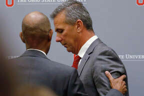 Paul Vernon Ohio State University President Michael Drake offers words to football coach Urban Meyer after a news conference in Columbus, Ohio. Ohio State suspended Meyer for three games for mishandling domestic violence accusations.