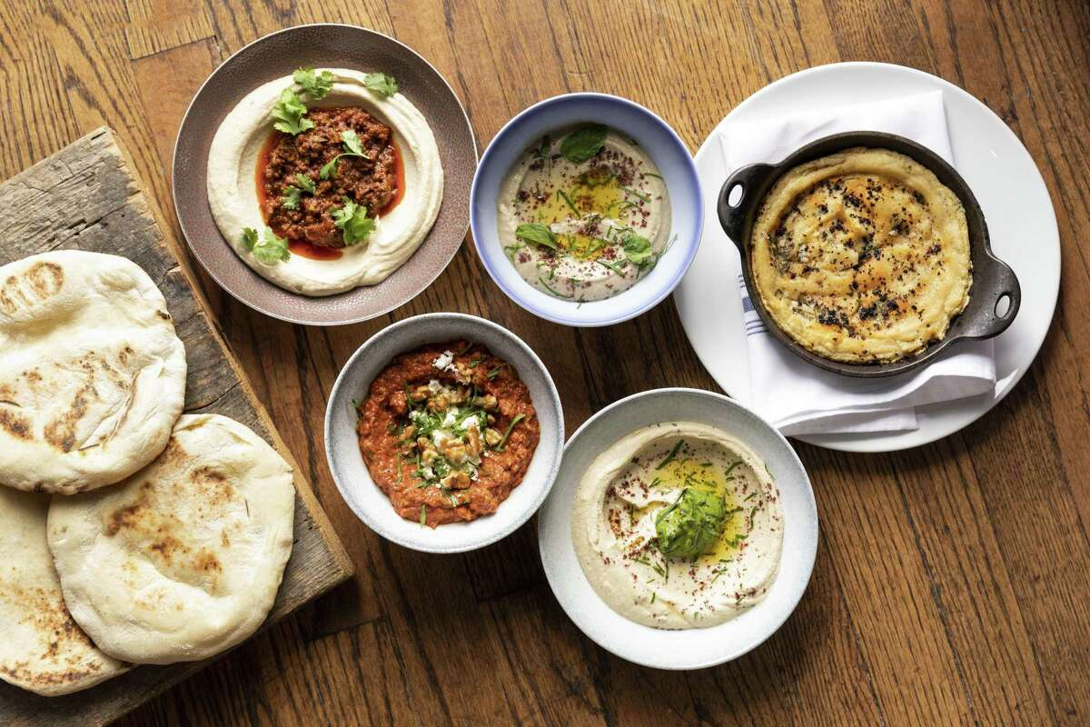 Top, from left: Hummus with ground lamb; Mutabal (eggplant dip); Turkish hummus Bottom, from left: Muhamara (roasted red pepper and walnut spread); hummus with green tehina at One Fifth Mediterranean.