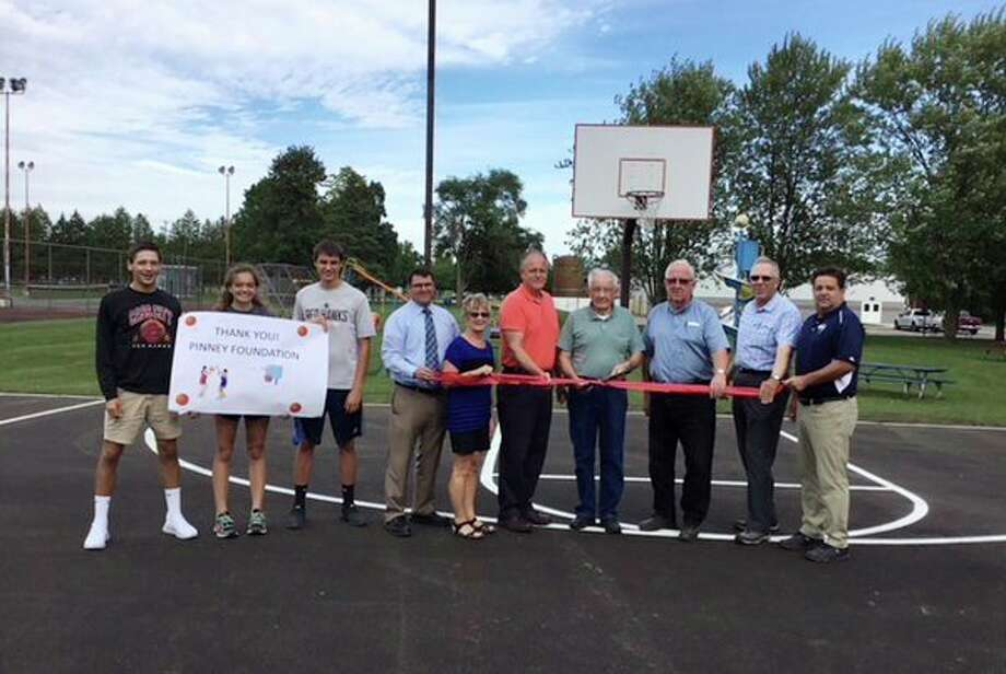 Representatives from the Pinney Foundation and Cass City's Village Council, along with student basketball players, recently held a ribbon cutting ceremony for the renovated basketball courts. Two grants from the Pinney Foundation totaling $19,900 helped the village pay for the court's resurfacing work. (Submitted Photo)