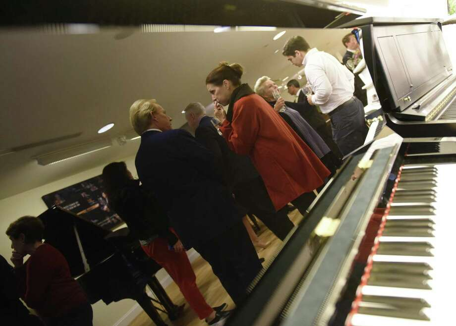 Folks chat in the reflection of a piano during the ribbon-cutting ceremony at the new Steinway & Sons showroom in Greenwich, Conn. Monday, Sept. 10, 2018. Located at 72 Greenwich Ave., the new showroom features a spectrum of buying options as well as full complement of community services such as in-home piano consultations. Photo: Tyler Sizemore / Hearst Connecticut Media / Greenwich Time