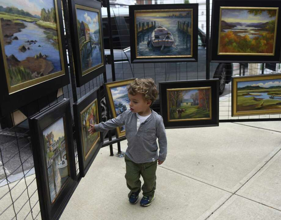 Riverside's Lucas McConnell, 2, looks at paintings from Daisy de Puthod on display at the Annual Sidewalk Art Show and Sale, sponsored by the Art Society of Old Greenwich, along Sound Beach Avenue in Old Greenwich, Conn. Sunday, Sept. 9, 2018. The two-day show and sale featured work by dozens of local artists of all mediums. There was also a Sidewalk Art Show for Young Artists, where children and teens exhibited their work, as well as a live performance by jazz pianist Lucas Gazianis, a member of the Jazz at Lincoln Center Youth Orchestra. Photo: Tyler Sizemore / Hearst Connecticut Media / Greenwich Time