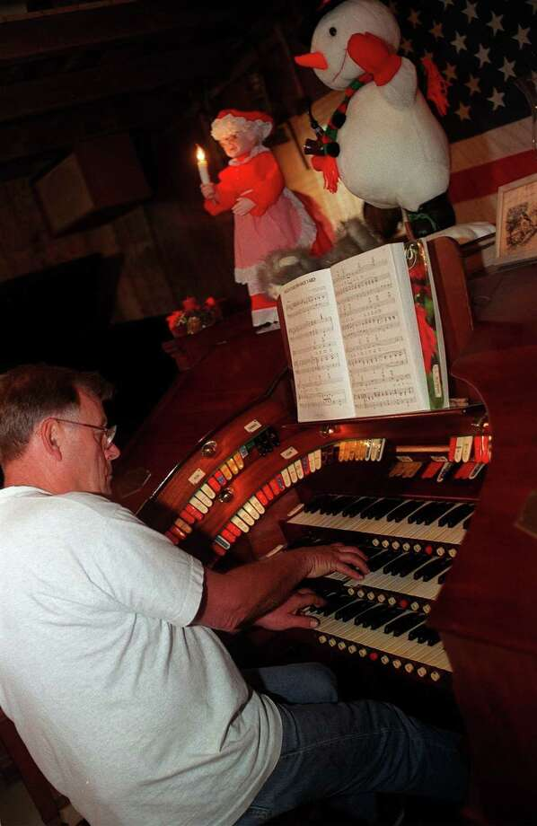 John R. Angevine plays the first sounds of Christmas music in this 1999 photograph. Photo: File Photo / File Photo / The News-Times File Photo