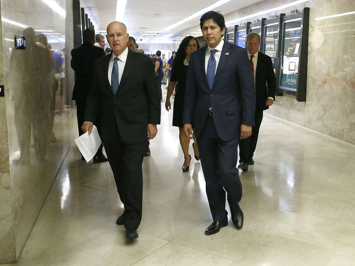 Calif., Gov. Jerry Brown, left, walks to a news conference where he signed SB100 an environmental bill authored by state Sen. Kevin de Leon, D-Los Angeles, right, Monday, Sept. 10, 2018, in Sacramento, Calif. SB100 sets a goal of phasing out all fossil fuels from the state's electricity sector by 2045. (AP Photo/Rich Pedroncelli)