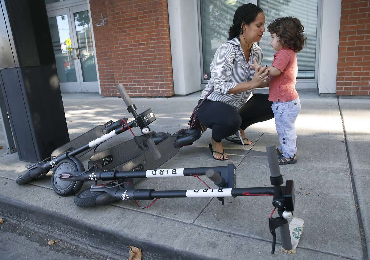 Siena Sarmiento speaks to her son Carter, 2, next to scooters lying on the sidewalk in Oakland, Calif. on Saturday, Sept. 8, 2018. Carter was knocked over and bruised when he was hit by someone riding an electric scooter as he and his mother walked out of their Grand Avenue apartment building.