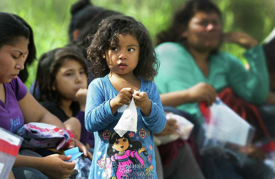 A young girl from Central America waits with other immigrants to be picked up by Customs and Border Protection officers, after crossing the Rio Grande River near Rincon Village in 2016. Photo: Bob Owen /San Antonio Express-News / ©2016 San Antonio Express-News