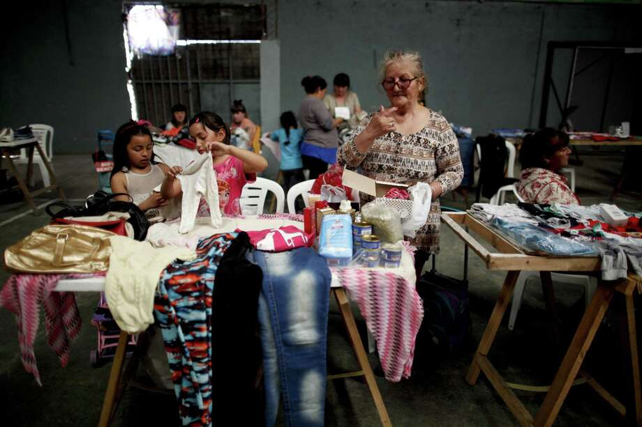 In this Sept. 6, 2018 photo, Lucia de Leon and her granddaughters Abril and Pricilla organize items they offer for exchange, at a barters market inside a community center on the outskirts of Buenos Aires, Argentina. De Leon said she has no money after paying her bills. Photo: Natacha Pisarenko /Associated Press / Copyright 2018 The Associated Press. All rights reserved