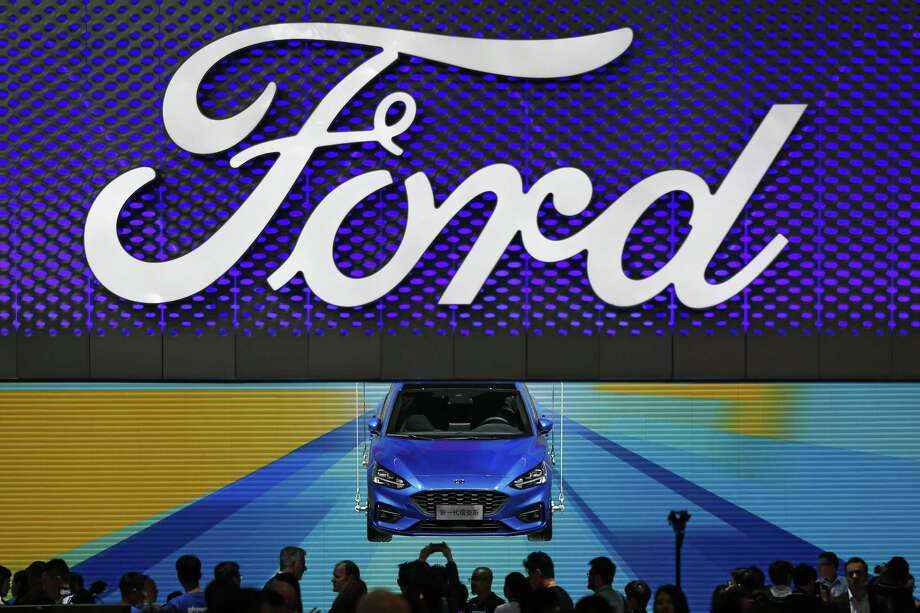 In this April 25, 2018, photo, visitors and journalists gather near a Ford Focus on display at the Ford exhibit during the media day for the China Auto Show in Beijing. Ford won't be moving production of a hatchback wagon to the United States from China, despite President Donald Trump's claim Sunday, Sept. 9, 2018 that his taxes on Chinese imports mean the Focus Active can be built in America. Photo: Andy Wong /Associated Press / Copyright 2018 The Associated Press. All rights reserved.