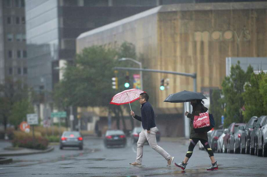 Pedestrians carry umbrellas while walking in the rain across Broad Street on Monday. This week's rain is expected to further help Stamford's reservoirs, which were more than 90 percent full as of last Wednesday. The average for this time of year is 80 percent. Photo: Michael Cummo / Hearst Connecticut Media / Stamford Advocate